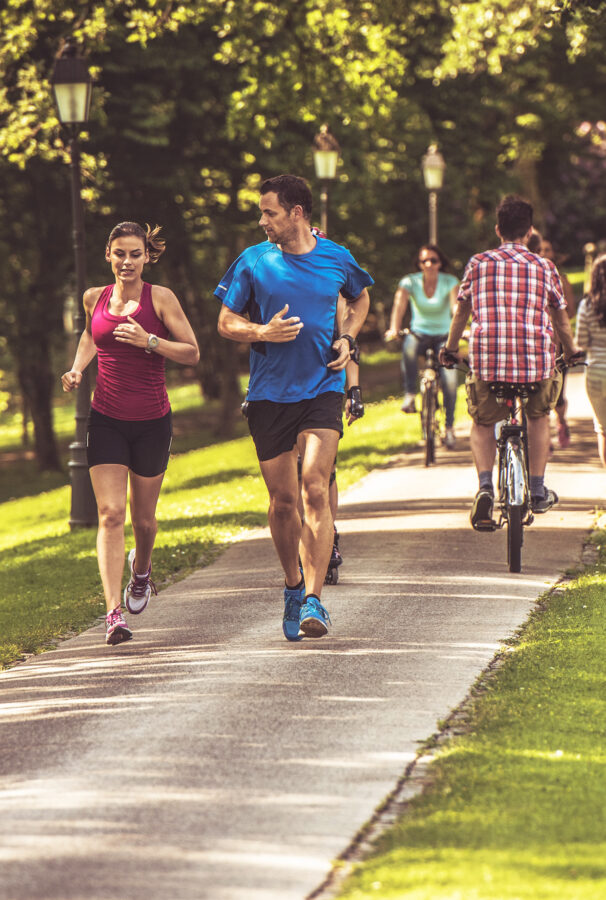 Couple going on a jog together through paved nature trails
