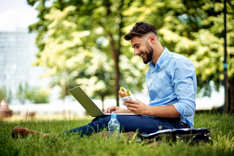 Young professional man enjoying lunch in the park with his laptop near corporate campus