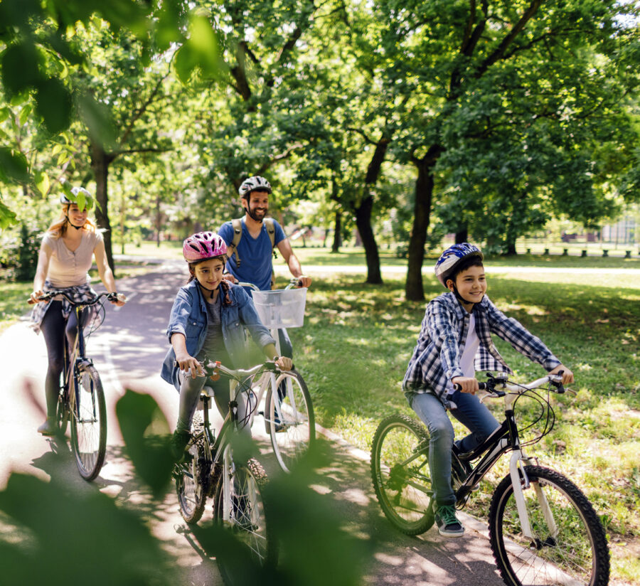 Family of four riding their bicycles through park trail