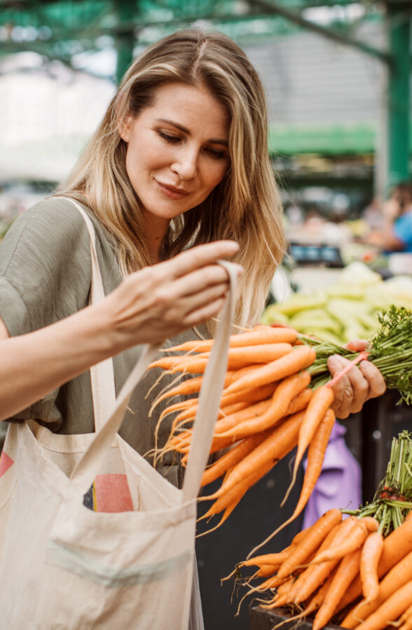 Woman buying groceries at outdoor fresh produce market