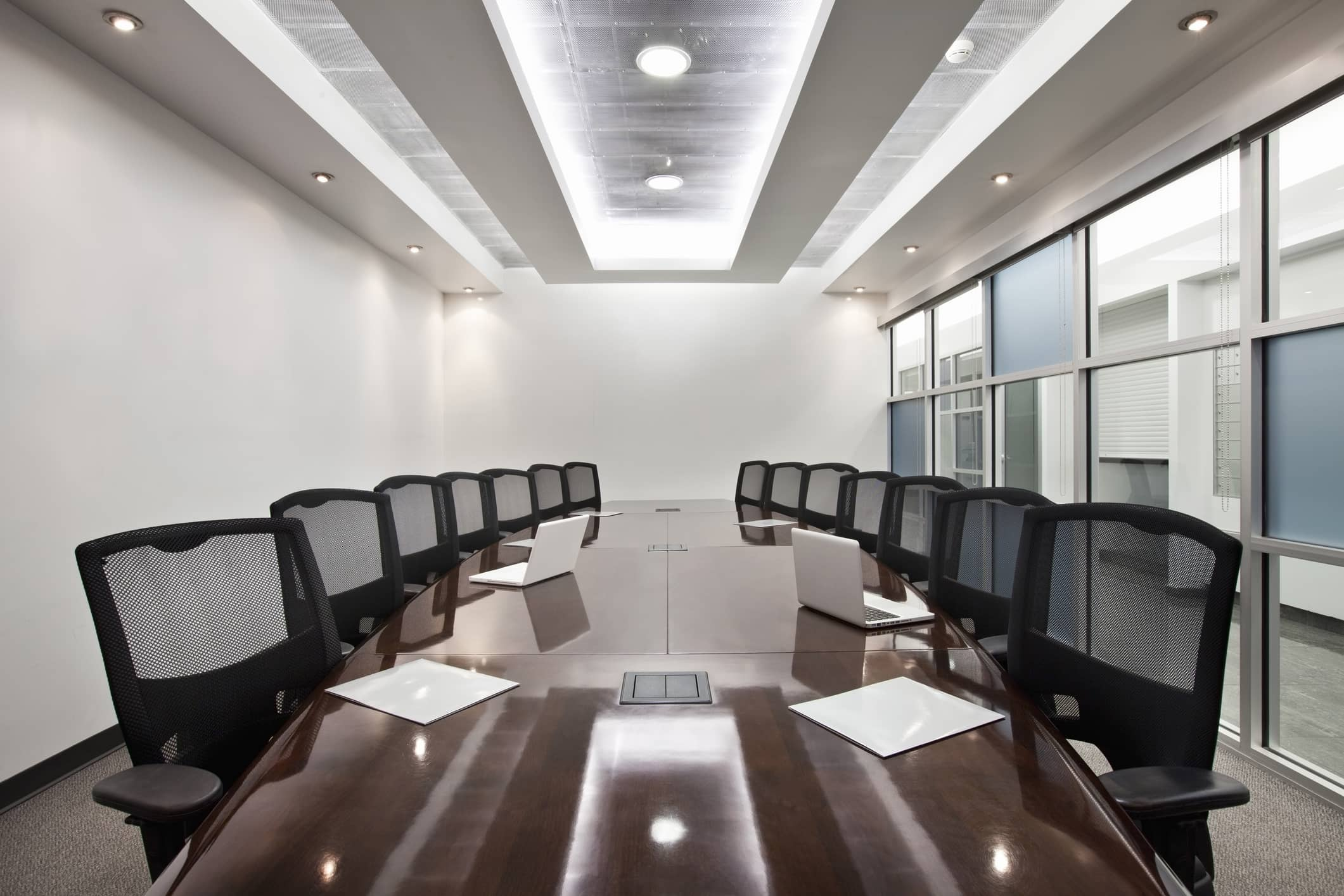 Large corporate executive meeting table in private room with glass windows