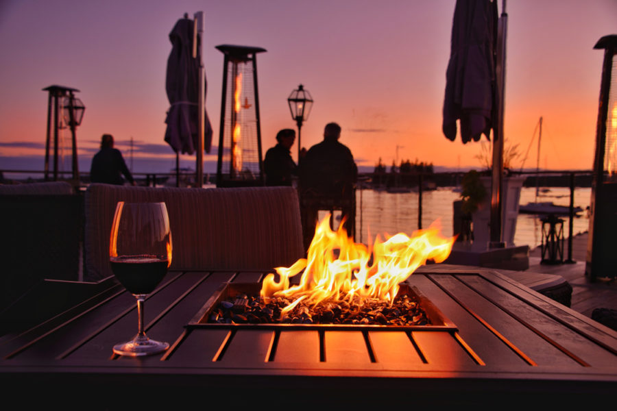couple at sunset near firepit on a dock