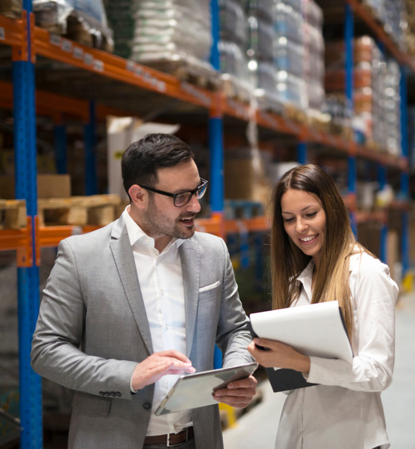man and woman discussing business in warehouse